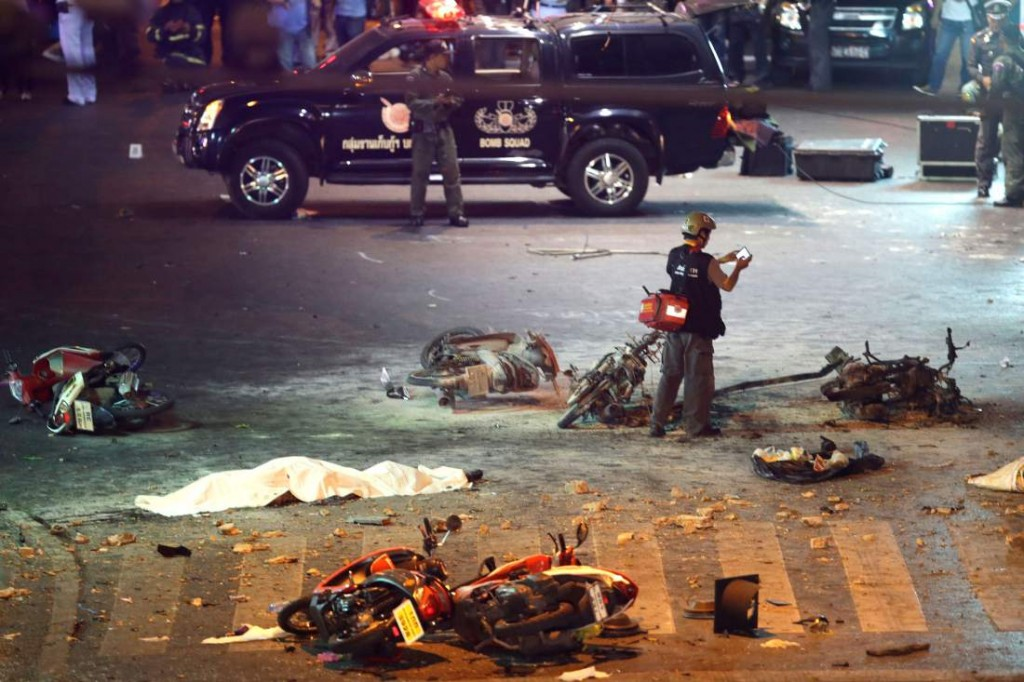 A policeman photographs debris from an explosion in central Bangkok, Thailand, Monday, Aug. 17, 2015. A large explosion rocked a central Bangkok intersection during the evening rush hour, killing at least three people and injuring 25 others, police said. (AP Photo/Mark Baker)